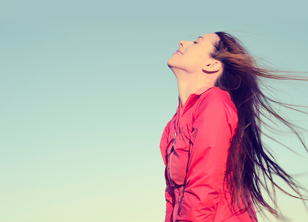 Woman smiling looking up to blue sky taking deep breath celebrating freedom. Positive human emotion face expression feeling life perception success peace mind concept. Free Happy girl enjoying nature